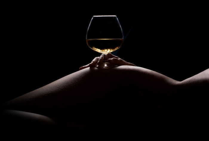 Beautiful, nude woman body silhouette and a glass of drink