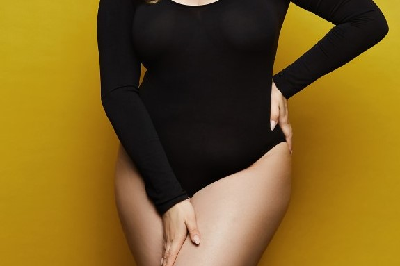 Plus size sexy model, fashionable blonde girl with bright makeup, in black bodysuit, with stylish hairstyle, smiling and posing at yellow background in studio.